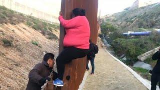 شاهد: مهاجرون يتسلقون السياج الحدودي في المكسيك للعبور إلى الولايات المتحدة…