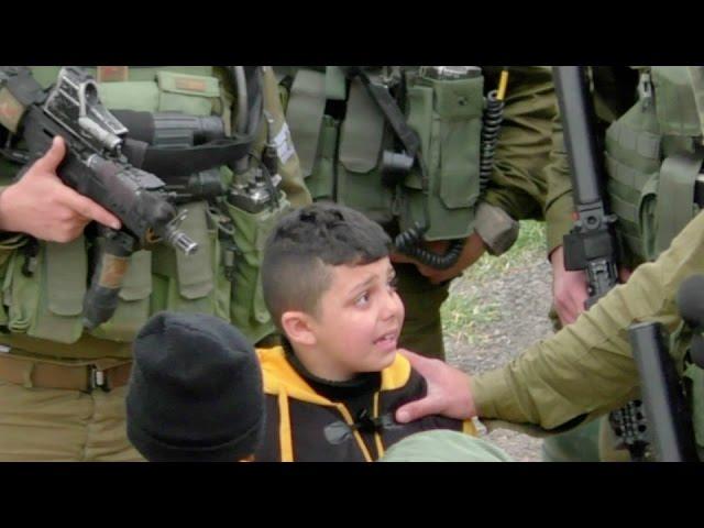 חיילים גוררים ילד בן שמונה מבית לבית בחיפוש אחר מיידי אבנים, חברון, מארס 2017