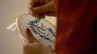 Girl making a beautiful embroidery design on a cloth piece