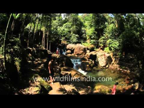 Tourists sit near waterfall in Sohra, Meghalaya