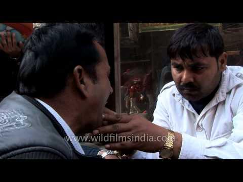 Varanasi street dentist treats a patient at his roadside clinic
