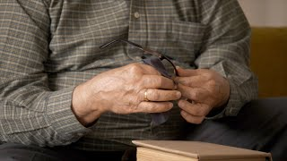 A senior man cleaning his spectacles with a cloth