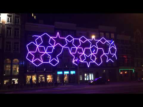 A neon fivefold composition on a building outside Amsterdam Central Station