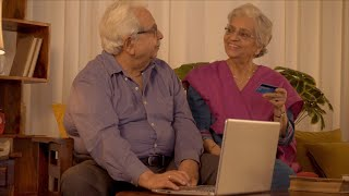 Happy Indian couple sitting in the living room and making credit card payment in laptop