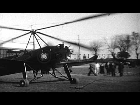 Pitcairn autogyro lands and men attempt to stop the autogyro's large rotor blades...HD Stock Footage