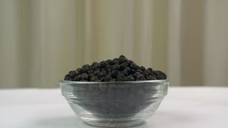 A pile of organic black pepper in a rotating glass bowl - selective focus on a white surface
