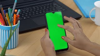 Woman hands browsing on her mobile phone with a green screen during lunchtime