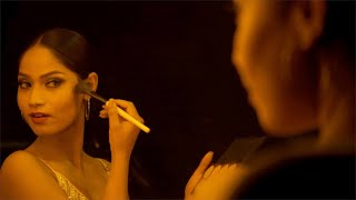 Young Indian model getting ready for a fashion show and applying makeup in front of a mirror