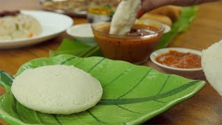 Close up of woman hands eating fresh steamed Idli with sambhar - food concept
