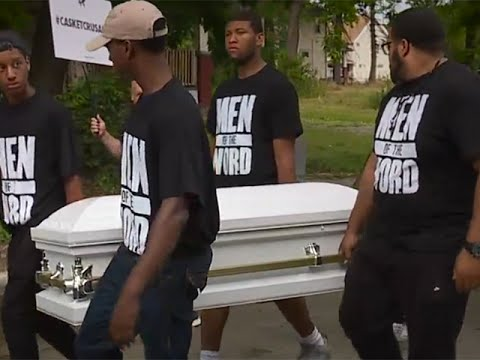 Thumbnail: Men carrying caskets march through the streets of East Cleveland