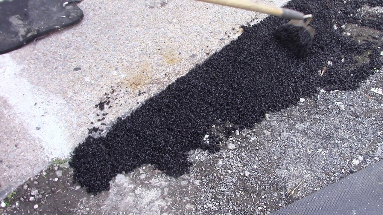 Driveway Repair Putting A Bag Of Blacktop Asphalt On Damaged Surface