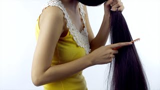 Side view shot - Attractive Indian girl brushing her black long hair using a comb