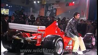 Sachin Tendulkar sits awkwardly atop a Ferrari race car at Indian Auto Expo