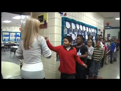 Amazing Female teacher doing the batch of handshakes with  a 3rd Grade  students