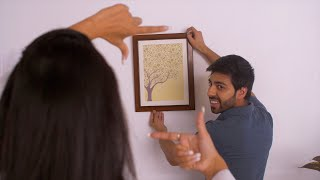 Moving to new house - Young Indian couple choosing point to hang a painting on the wall