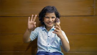 Young handsome kid happily eating ice cream with a cheerful ok gesture - lifestyle kids
