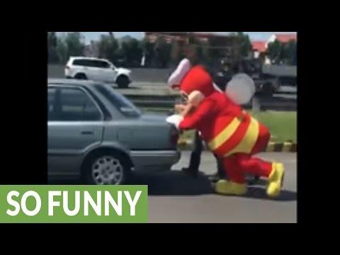 Mascot helps push broken vehicle