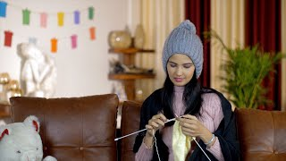 Pretty Indian woman in a warm grey hat knitting sweaters at home - wintertime