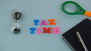 Tax time - Plastic colorful letters with a diary, pen, sand clock and magnifying glass