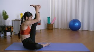 A young attractive female practicing yoga in sportswear on a blue yoga mat at home