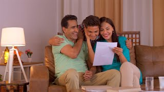 Middle aged Indian parents interrupted by son showing his grade - Happy Indian Family