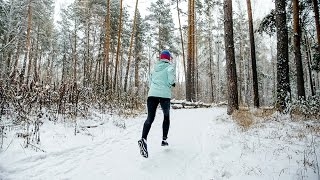 young female athlete runner running a winter marathon in a snowy Park