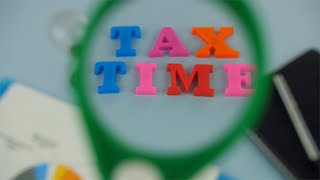 "Woman hands moving magnifying glass left to right over the words ""Tax Time"""
