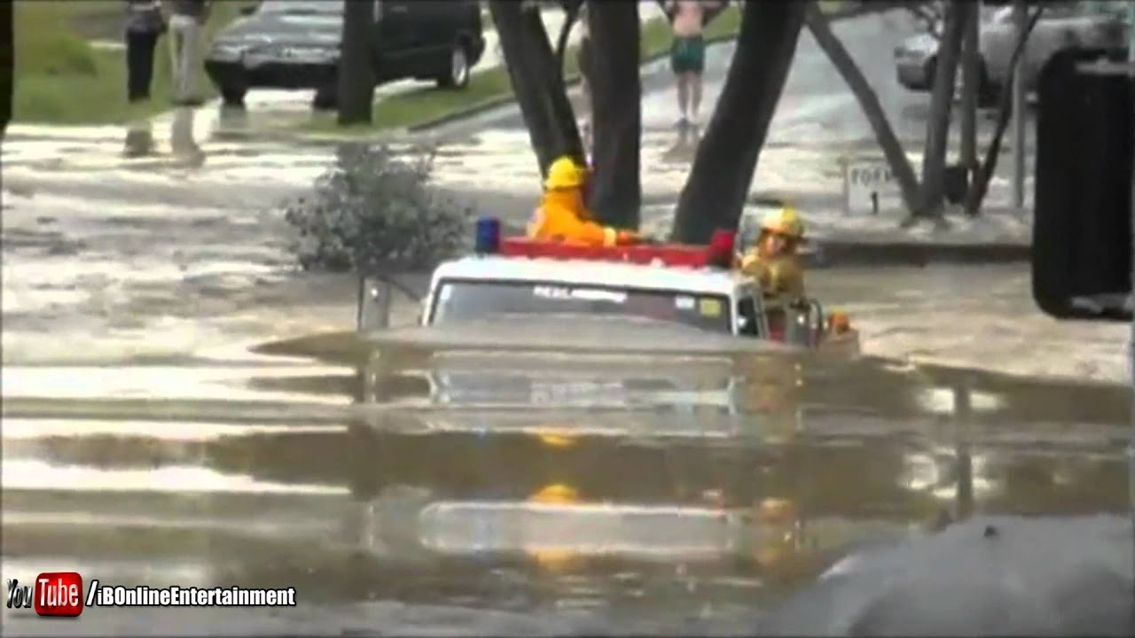 Wóz strażacki przejeżdża przez zalaną drogę