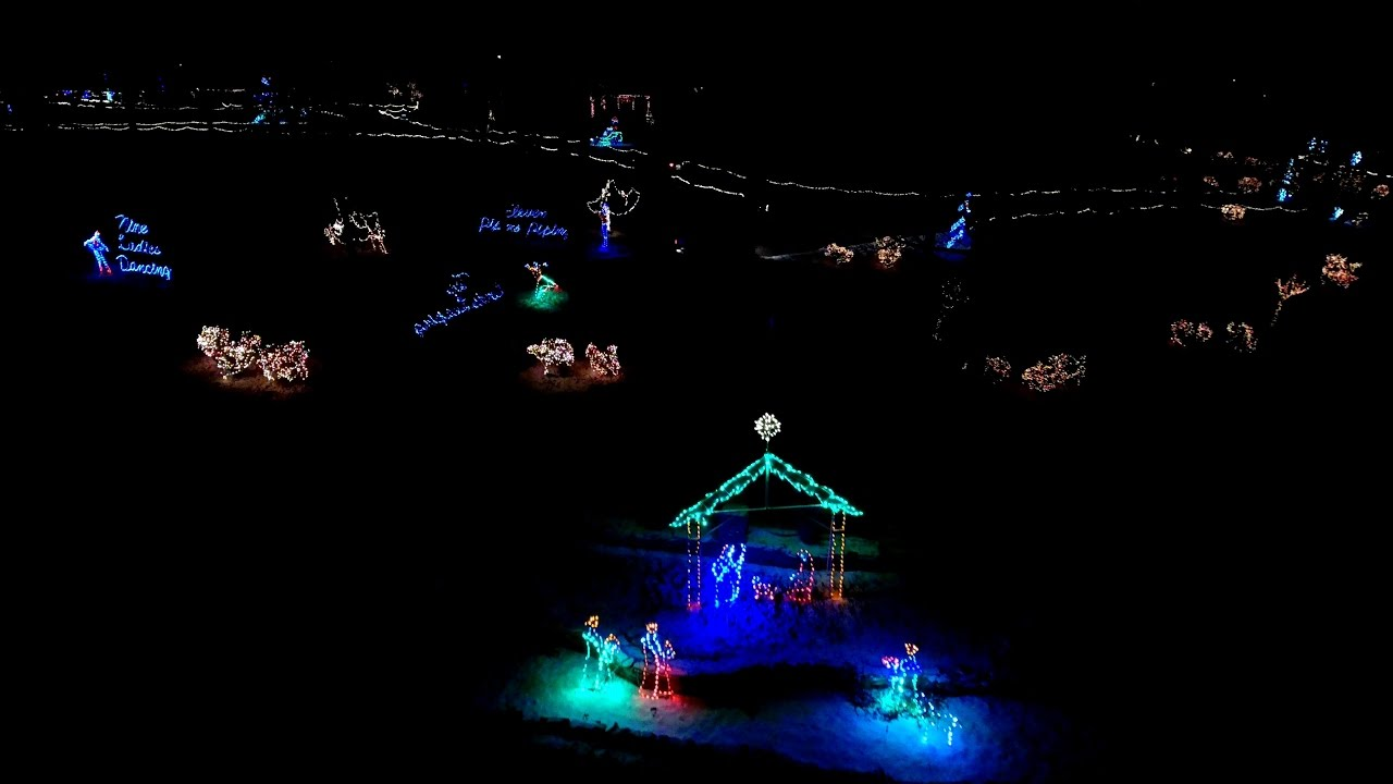 drone flight over frankfort tpa park christmas lights with snow blanket