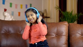 A cute little girl enjoying music using her Bluetooth headphones - technology concept