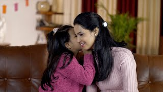 Closeup shot of a smiling Indian girl sharing her secrets with her mom - family concept