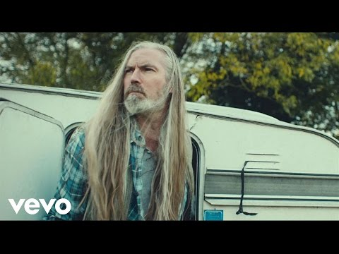 Screen shot of man with long, gray hair in front of an RV. Image has a Vevo watermark