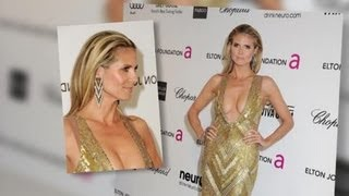 Heidi klum shows off some major skin in a very low-cut gold gown at elton john aids foundation oscar viewing party.splash is the leading independent entertai...