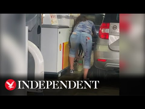 Woman empties water bottles and fills them with petrol at pump
