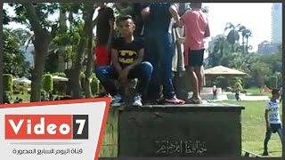 أطفال يعتلون تمثال حافظ إبراهيم لالتقاط السيلفى بحديقة الحرية