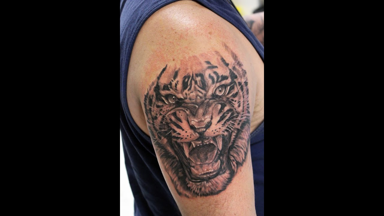 Roaring tiger arm tattoo in black and gray by Jesus