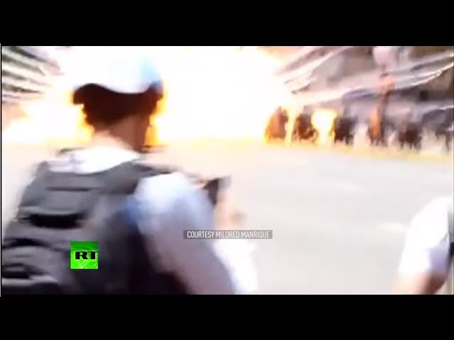 Police motorcycles hit by an explosive device as protesters cheer in Venezuela