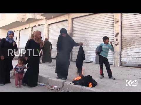 Syria: Women burn black burqas after the SDF liberate Manbij from IS