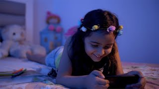 Smiling beautiful girl with tiara using a mobile phone at night in the bedroom - technology concept