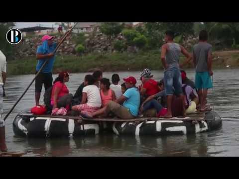 Migrantes hondureños cruzan en balsa el río fronterizo entre Guatemala y México