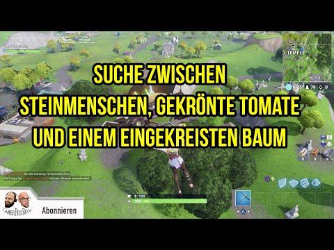 suche zwischen einem riesigen steinmenschen einer gekrönten tomate und einem eingekreisten baum