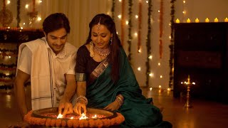 South Indian couple in traditional wear lighting a lamp - Diwali Concept