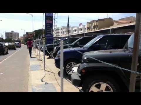 Senegal Video # 7, luxury car lot and cow
