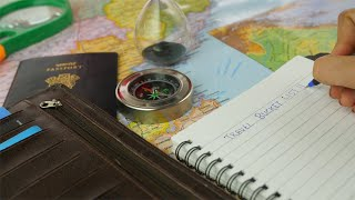Hands of an Indian woman making a travel bucket list - travel planning concept
