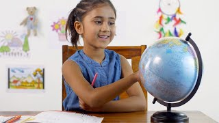 School going Indian girl exploring and looking at the globe - Learning geography