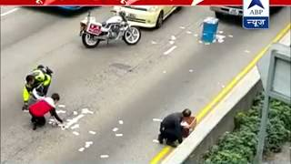 Cash van spills notes on busy Hong Kong road, sparks money grab