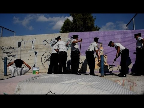 Gang graffiti erased by police officers near Guatemala City
