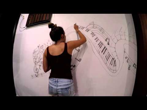 Airbrushing a mural of a piano in a music room