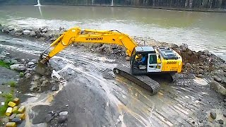 Hyundai Excavator and Hino Dumper moving stone on a River manufacturing a DAM