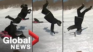 Reporter flipped by sled during news report [OFFICIAL VIDEO]
